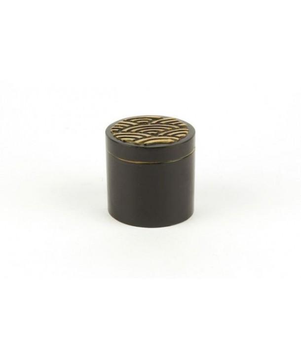 Boîte pilules motif vague en pierre fond noir